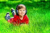 stock photo of 7-year-old  - 7 years old boy lying on a grass and listening to music in headphones - JPG