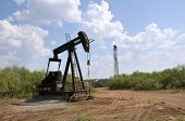 stock photo of oil well  - Wichita Falls, TX - Oil pump gets the oil from the ground in north central Texas, as they drill another well in the background.