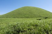 picture of hemisphere  - Green hemispherical hill in the grassy plain under blue sky - JPG