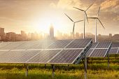 stock photo of generator  - solar panels and wind generators against city view on sunset - JPG