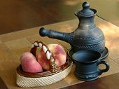 foto of loamy  - Arabian coffee pot and ceramic vase with peaches on a table - JPG