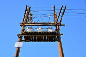 pic of transformer  - A wooden platform on poles supports three high voltage transformers - JPG