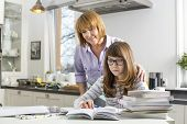 pic of homework  - Mother assisting daughter in doing homework in kitchen - JPG
