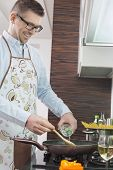 image of saucepan  - Happy man adding white wine to saucepan while cooking in kitchen - JPG