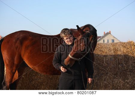 Teenager Boy In Black Hugging Brown Horse