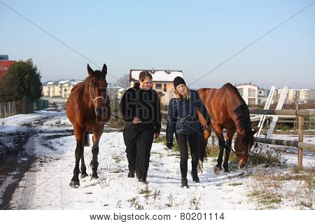 Two Teenagers And Two Horses Walking In The Snow
