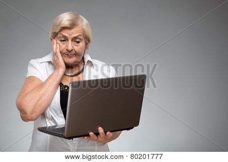Elderly woman holding the laptop