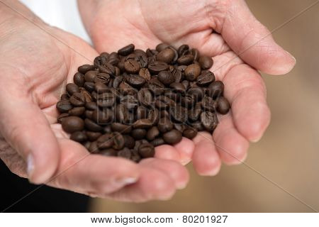 Elderly woman holding coffee beans