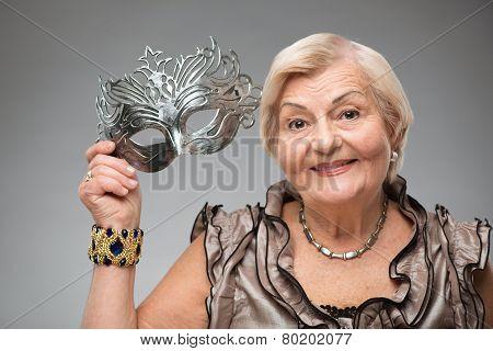 Elderly woman wearing glamorous mask