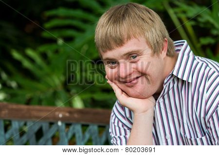 Facial Portrait Of Handicapped Boy Resting Chin On Palm Of Hand.