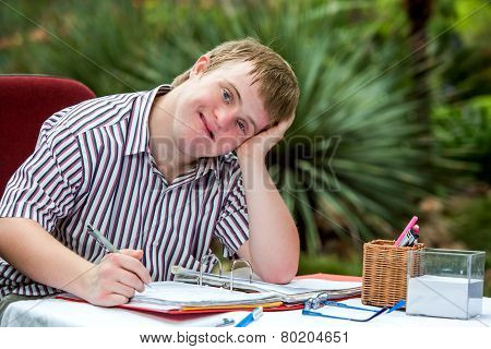 Handicapped Boy Resting On Hand At Desk.