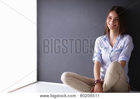 Portrait of young woman sitting on the floor near dark wall