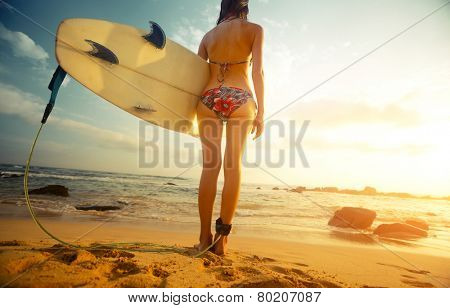 Young lady standing with surf board on the tropical beach