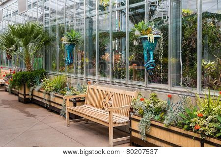 Empty Wood Benches By Greenhouse In Garden