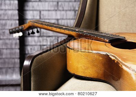 Close-up Of Acoustic Guitar Lying On The Sofa