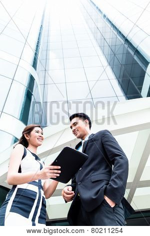 Asian business woman and man working outside on pad