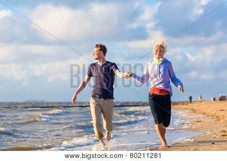 Couple enjoying romantic sunset at north sea beach