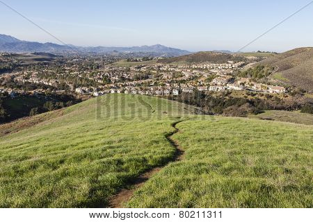 Suburban meadow hiking trail leading to upscale modern homes near Los Angeles in Thousand Oaks, California.