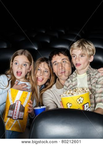 Surprised family of four with popcorn watching movie in cinema theater