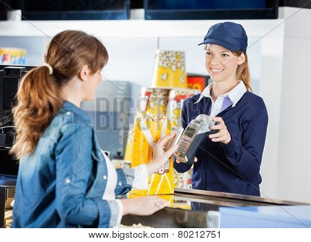 Smiling female worker accepting payment from woman through NFC technology at cinema concession stand
