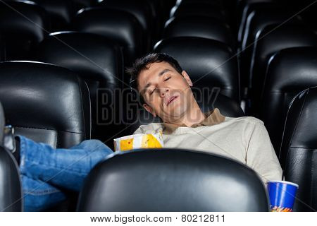 Bored mid adult man sleeping at cinema theater