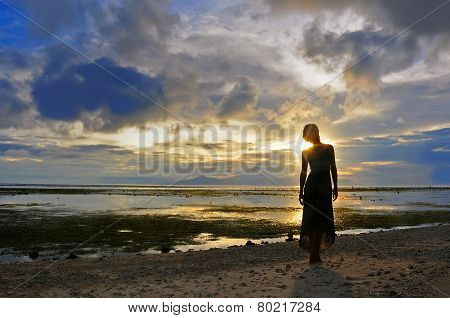 Woman stay at the Sunset over Bali as seen from Gili, Indonesia