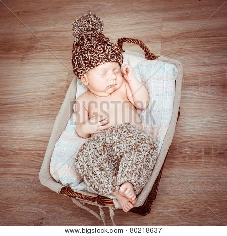 newborn boy in pants and hat asleep in the basket