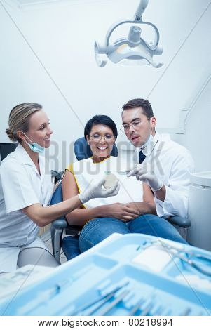Female dentist with assistant showing woman prosthesis teeth