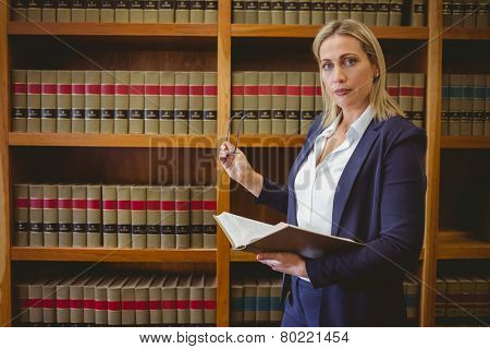 Focused librarian holding book and reading glasses in library