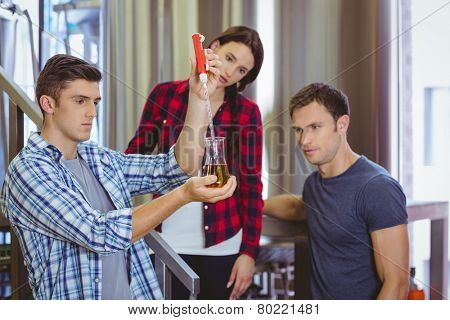 Man pouring beer into the beaker with a pipette in the factory