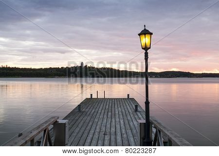 Wooden Jetty With One Lamp On It.