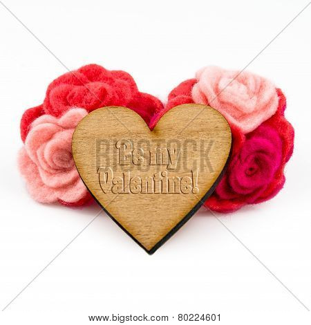 Wooden heart with carved words and red wool flowers on white background. Valentine's Day greeting ca