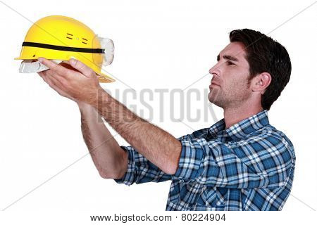 Man holding up a construction helmet