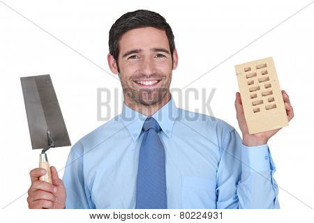 A man in a suit holding a brick and a trowel.