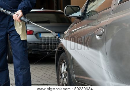 Closeup Of A Mechanic Washing A Car By Pressured Water At Garage
