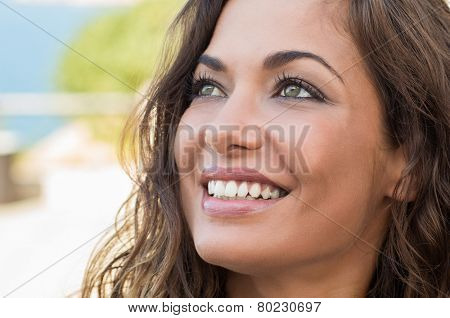 Close Up Of Young Beautiful Woman Daydreaming and Smiling In Summer Time