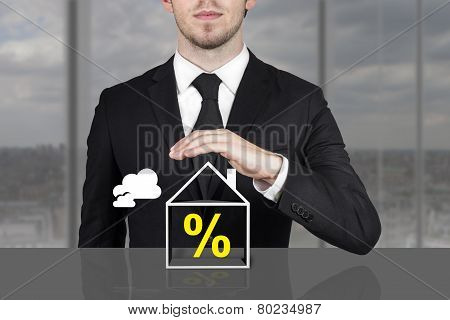 Businessman Holding Protective Hand Above Building Percentage Symbol
