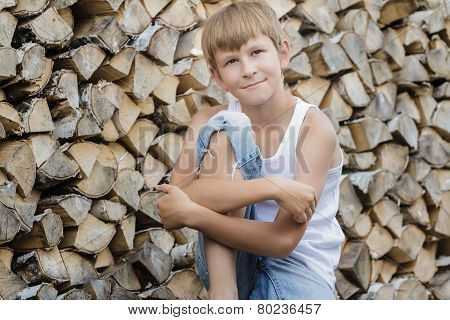 Portrait of teenage boy at firewood background