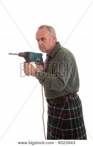 Maduro Scotsman utilizando un taladro eléctrico