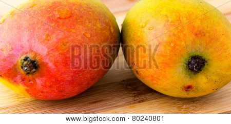 two mango on carving board
