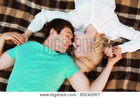 Lovely Young Couple In Love Resting On The Plaid, Warm Tender Feelings. Top View