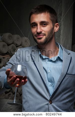 young man stands with glass of wine