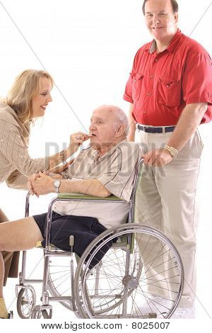 woman helping man in wheelchair eat