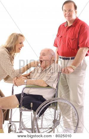 woman feeding elderly man in wheelchair