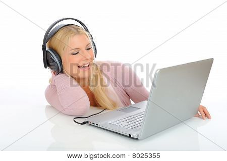Pretty Young Girl Listening To The Music With Headphones From Her Laptop. Isolated On White Backgrou
