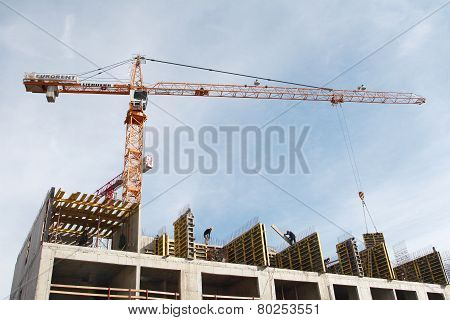 Construction Of Monolithic Apartment House, Tower Crane Lifts The Load.