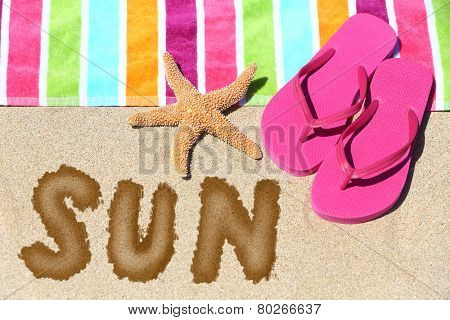 Word - Sun - on a tropical beach with a striped towel in the colors of the rainbow, pink slip slops and a sea star on sunny golden sand symbolic of travel and a summer vacation in the tropics
