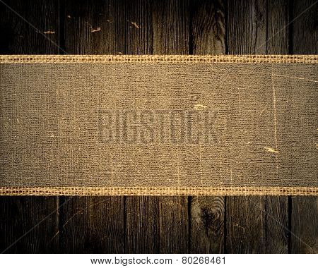old grunge jute canvas banner textured with dark wood background