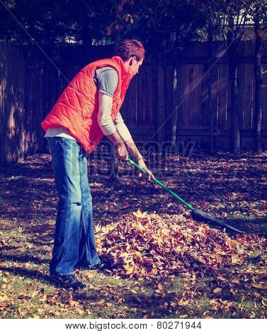 a man raking autumn leaves toned with a retro vintage instagram filter effect