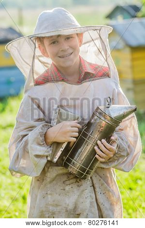 Young beekeeper checking hives on bee yard